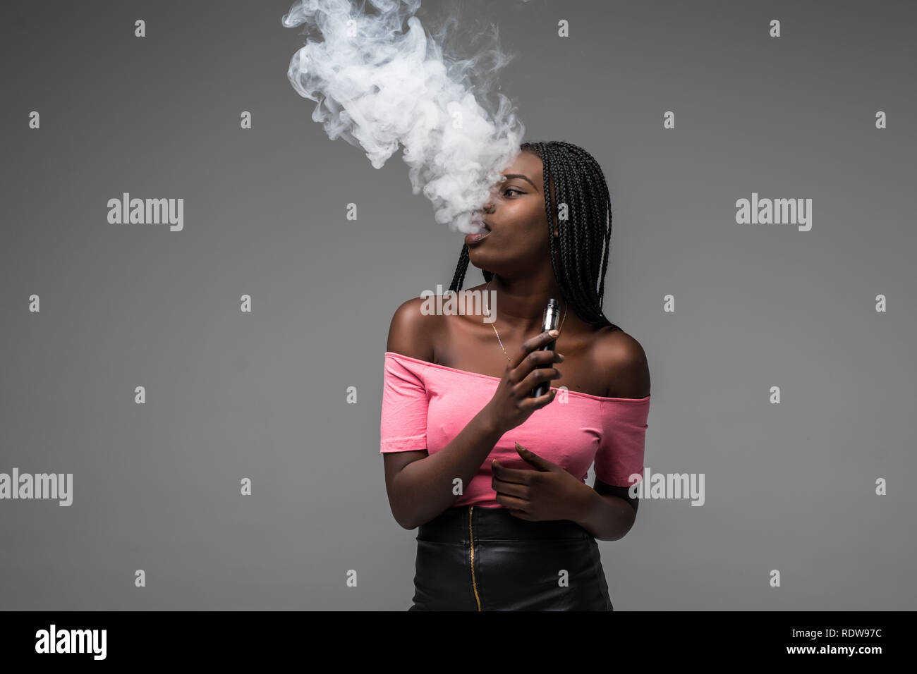 Young beauty african woman smoke vape, e-cigarette, on gray background - Stock Image