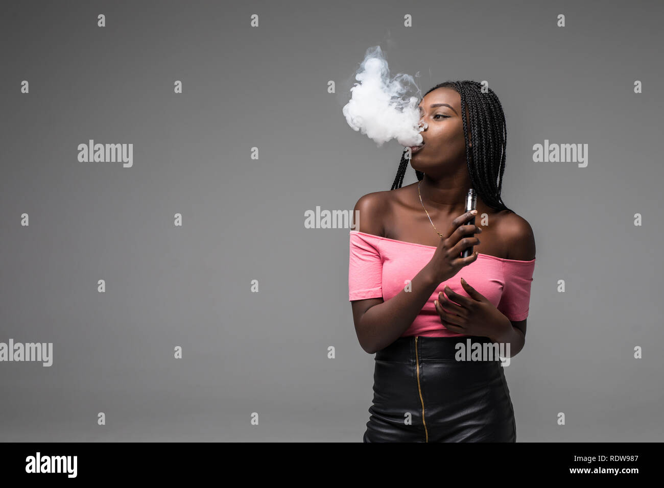 Portrait of young african woman standing with vape device in hand on gray background - Stock Image