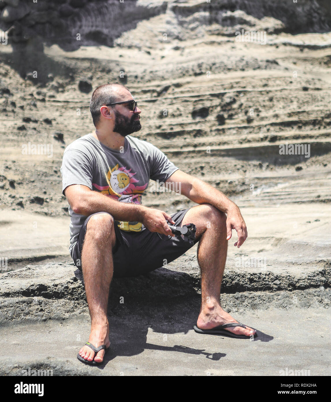 Young man with beard siting on the sandy desert bank Bali Indonesia - Stock Image