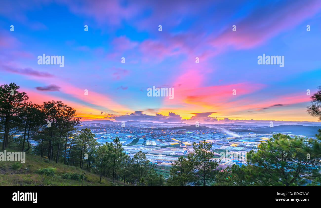 Sunset scene in valley with greenhouses to plant flowers and vegetables. The moment when the sun go down to horizon, the rays of sunlight were shining Stock Photo