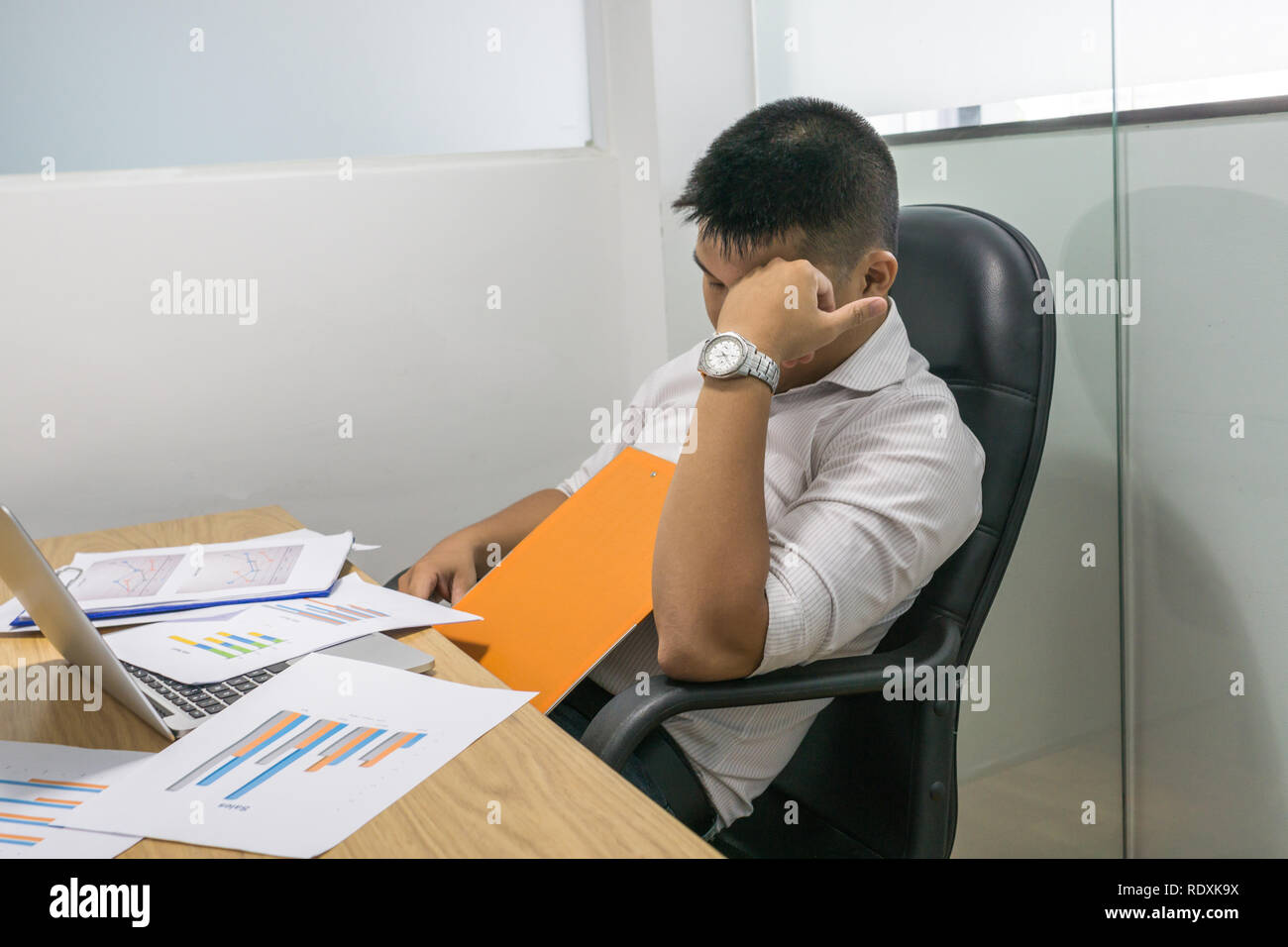 Tired and stressful man overloaded with business work - Stock Image