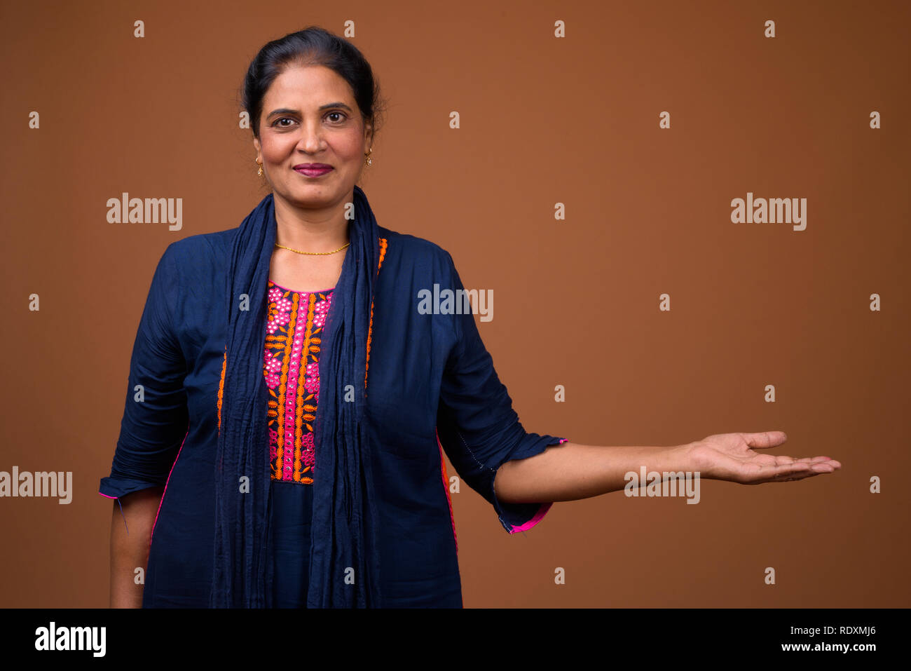 Portrait of mature beautiful Indian woman holding copyspace - Stock Image