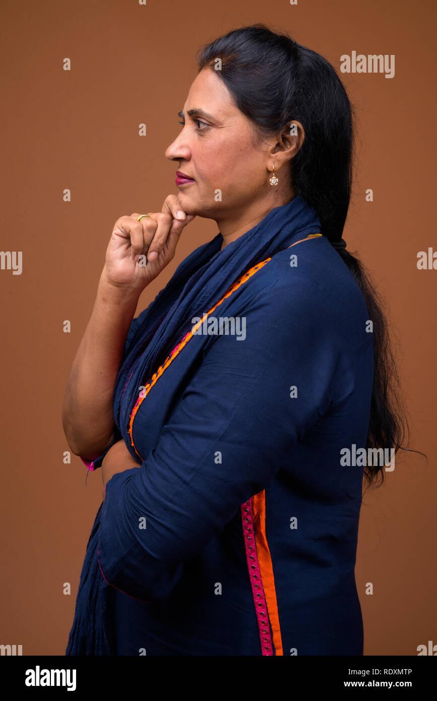 Profile view of mature beautiful Indian woman thinking - Stock Image