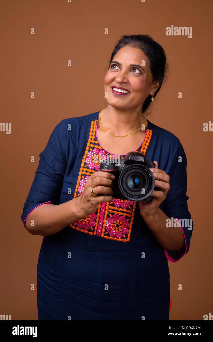 Mature Beautiful Indian Woman Photographer Using Dslr Camera Stock