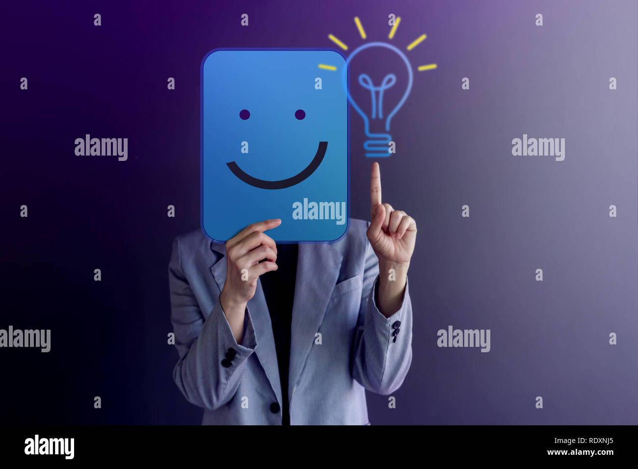Ideas, Creativity and Innovation Concept. Happy Woman Covered her Face, presenting Smiling Face, LightBulb and Body Language by Finger Up - Stock Image