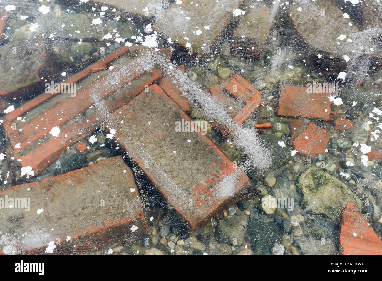Winter background. Bricks and stones under the ice - Stock Image
