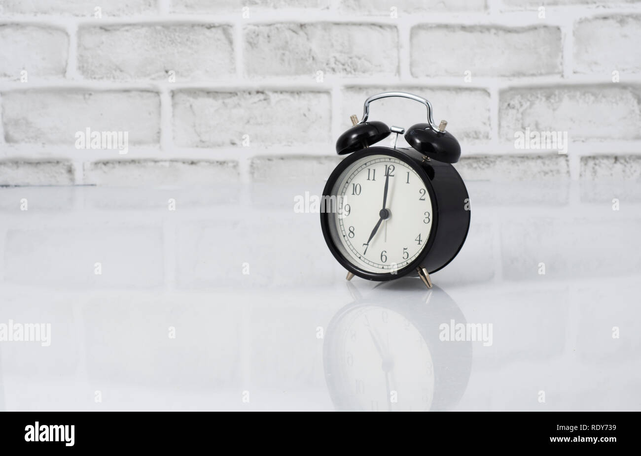 A vintage black alarm clock reading 7 am on a white brick wall background Stock Photo