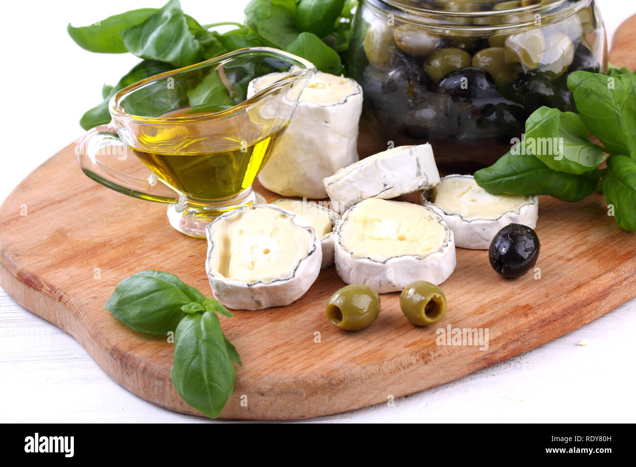 Still-life with saint-mor-de-turen cheese with black olives on white background - Stock Image