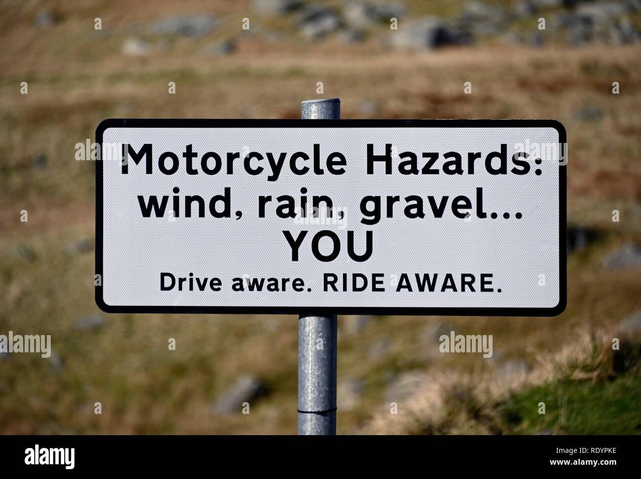 Warning road sign. 'Motorcycle Hazards: wind, rain, gravel...YOU Drive aware. RIDE AWARE.'   Kirkstone Pass, Cumbria, England, United Kingdom, Europe. - Stock Image