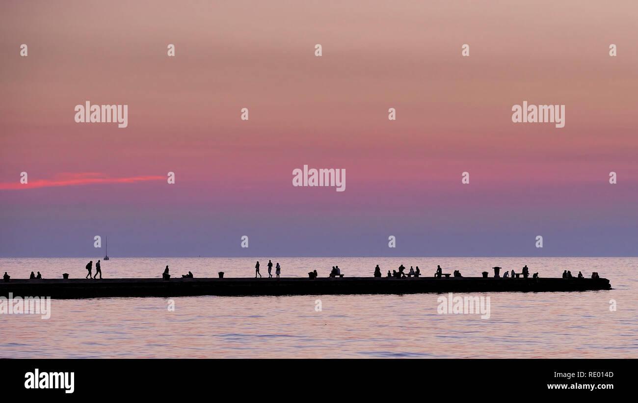 Enjoying the calm evening on a pier - Stock Image