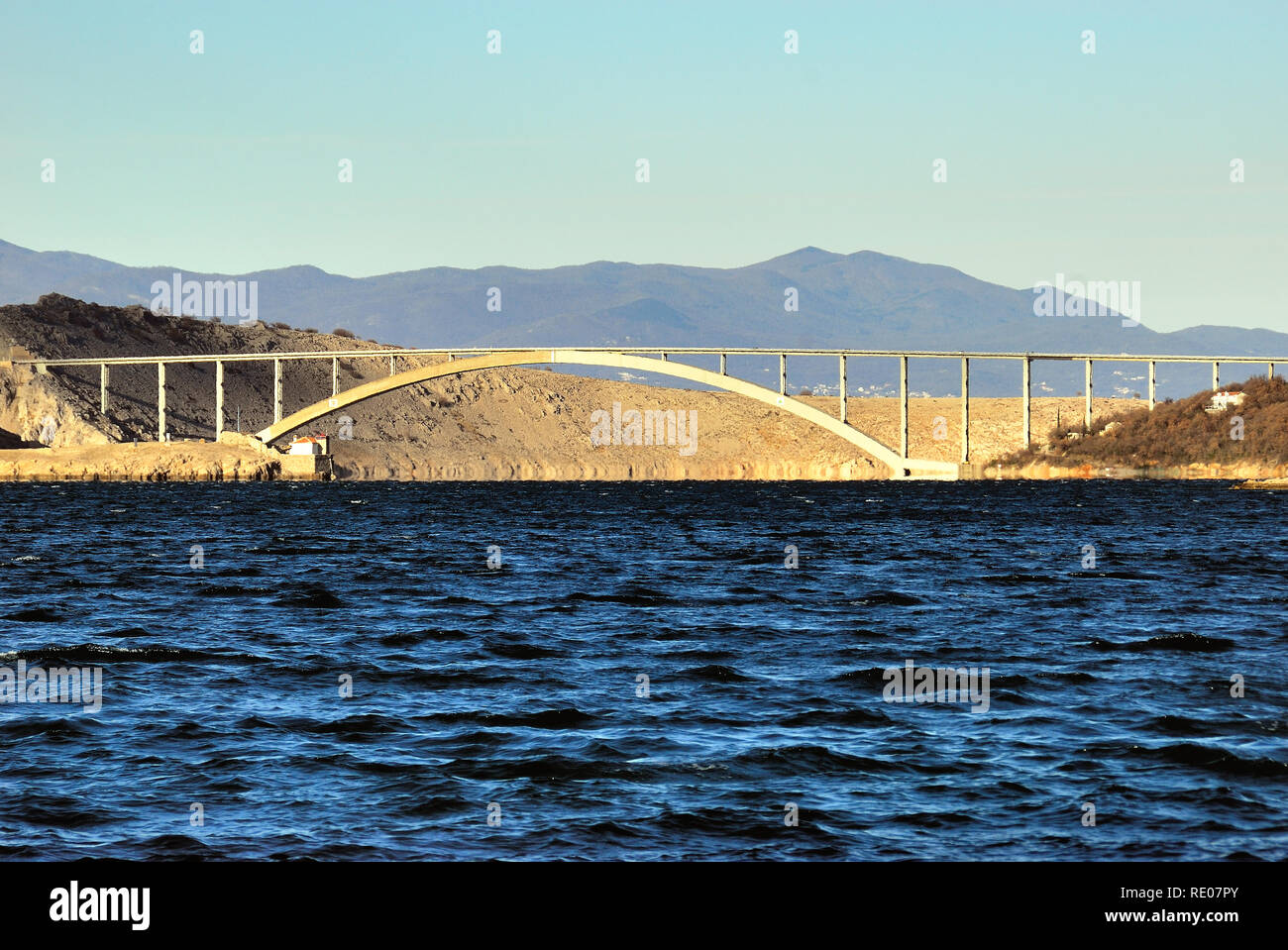 """Croatia, Dalmatian coast, Jadranovo village, the bridge that connects the mainland with the island of Krk. Krk Bridge is a 1430 m long reinforced concrete arch bridge connecting the Croatian island of Krk to the mainland and carrying over a million vehicles per year. The longer of the bridge's two arches is the second longest concrete arch in the world and among the longest arches of any construction. The bridge was completed and opened in July 1980 and originally named Titov most (""""Tito's bridge"""") in honor of Yugoslav president Josip Broz Tito, who had died two months earlier. Stock Photo"""