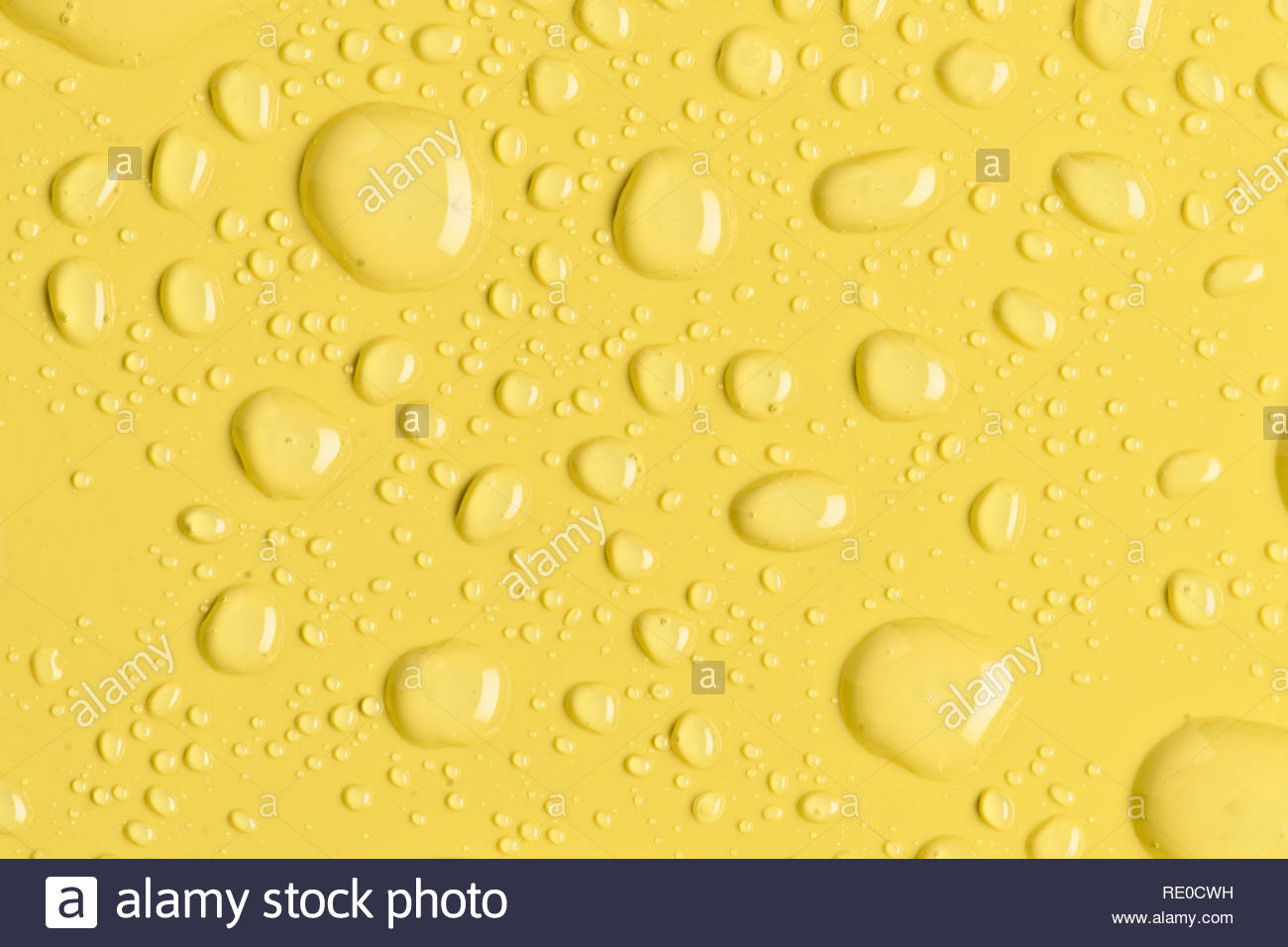 Bright water droplets on yellow synthetic material surface - Stock Image
