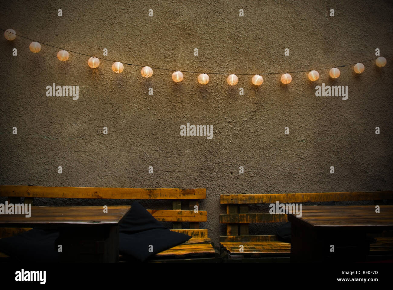 A decorative chain of lights strung across a wall in a beer garden at the back of a bar in Krakow, Poland - Stock Image