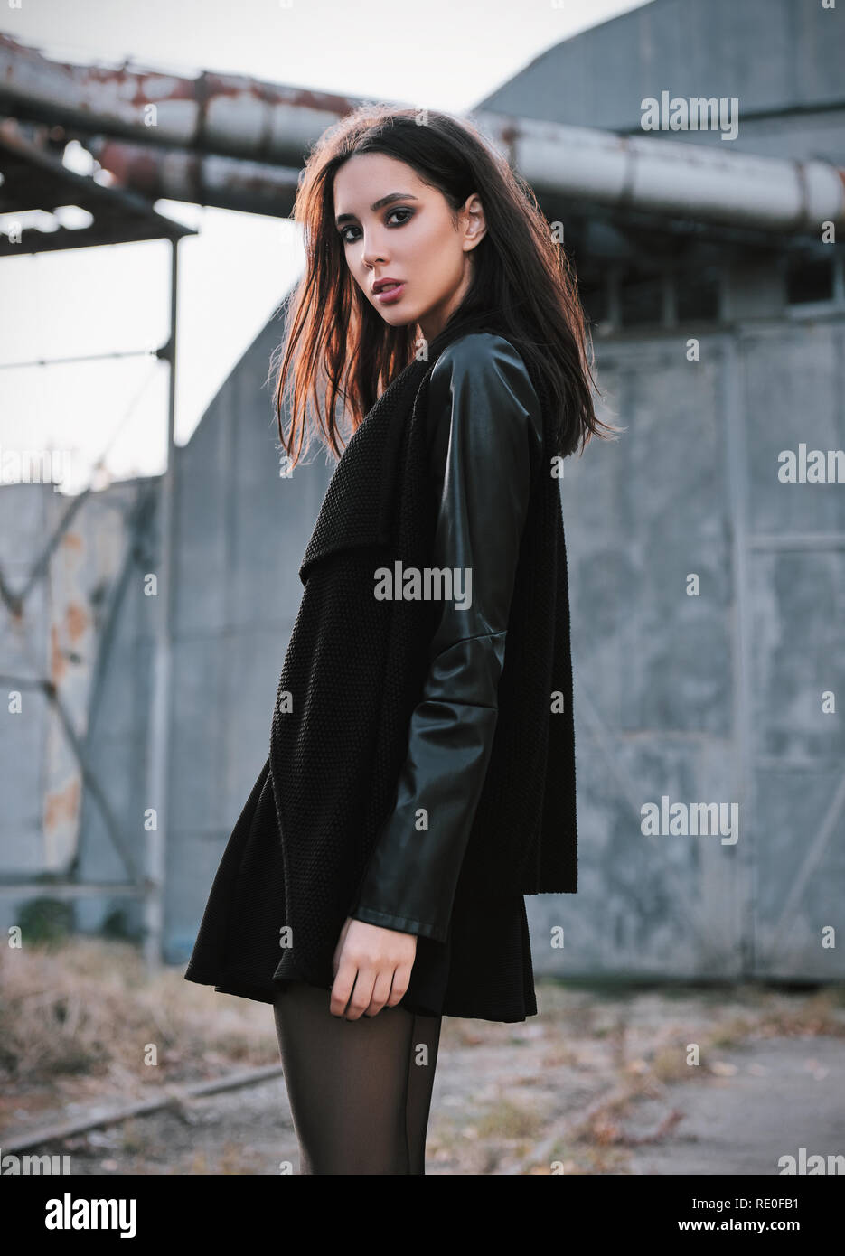 Fashion shot: portrait of the beautiful rock girl (informal model) dressed in black jacket standing at industrial place - Stock Image