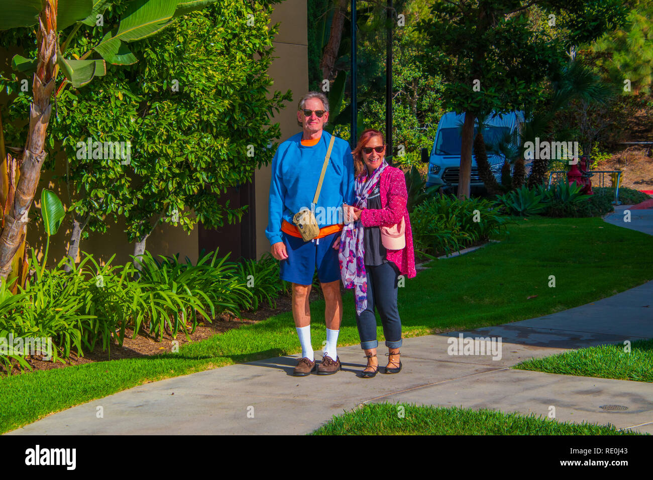 Senior citizen male caucasian baby boomer with Alzheimer's Disease wearing shorts and high white athletic socks being helped to walk by younger female - Stock Image