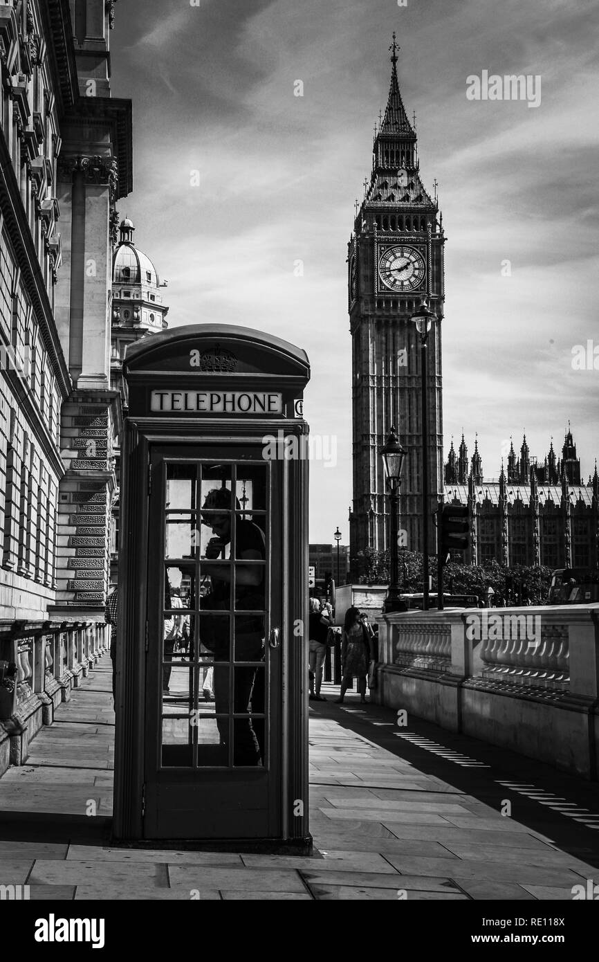 A man using the phone in a typical British telephone box on the sidewalk with the famous Elizabeth Tower (Big Ben) in the background - London, UK - Stock Image