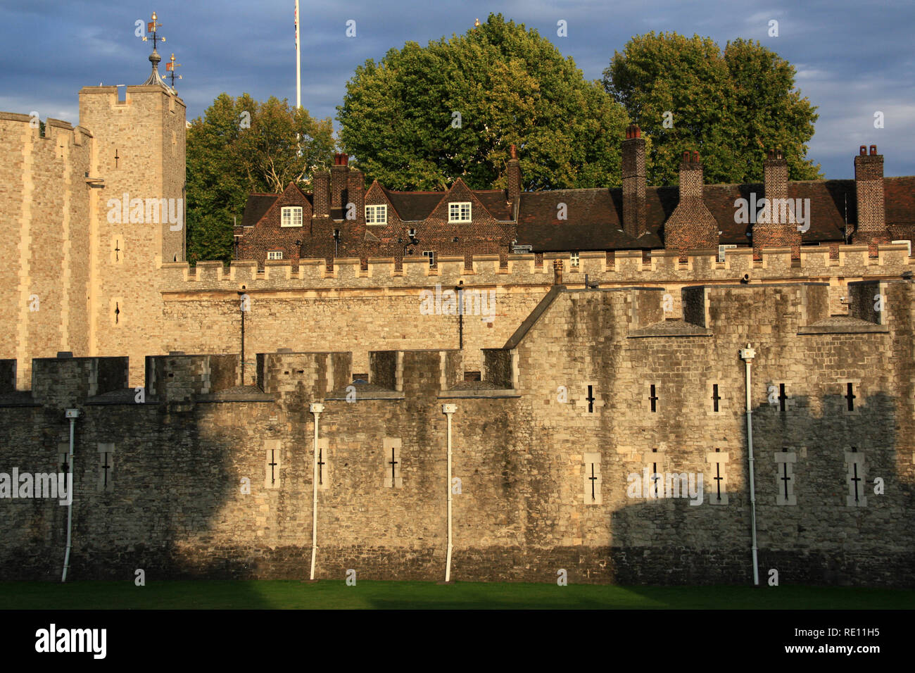 Rooftop and Chimneys of the Queen's House behind the fortified wall of Her Majesty's Royal Palace and Fortress of the Tower of London, UK - Stock Image