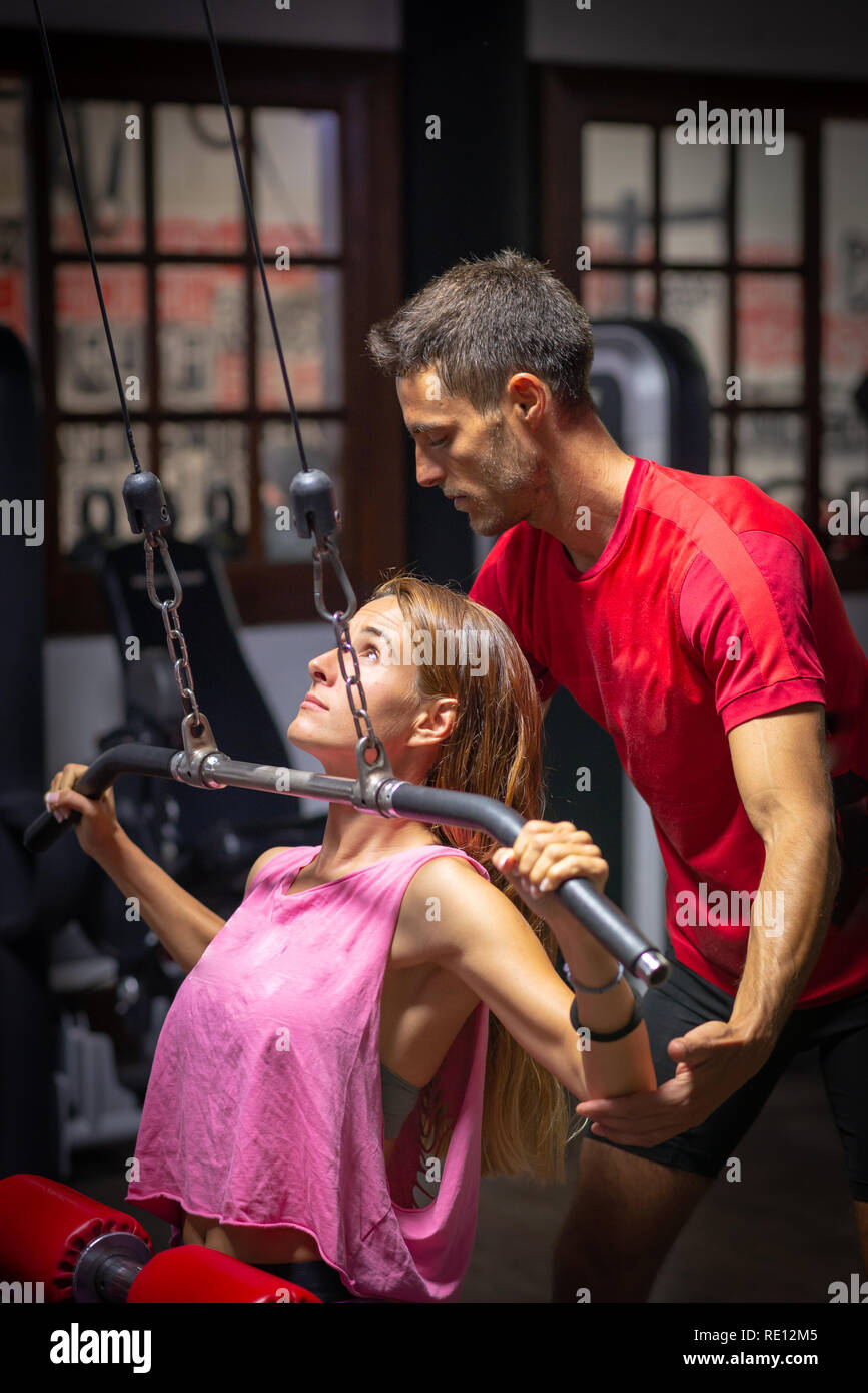 girl in training assisted by personal trainer - Stock Image