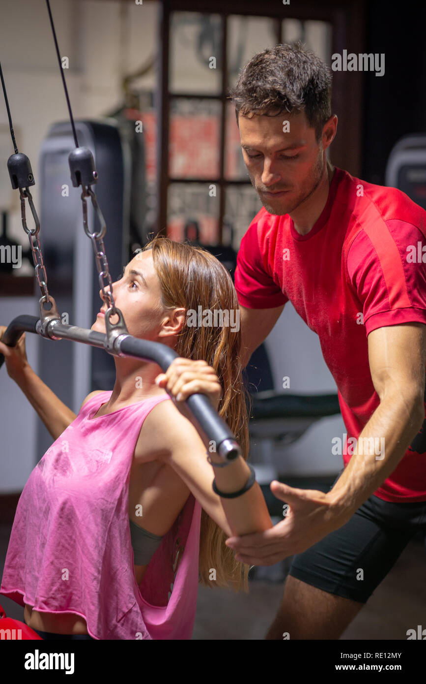 personal trainer assists a girl in training - Stock Image
