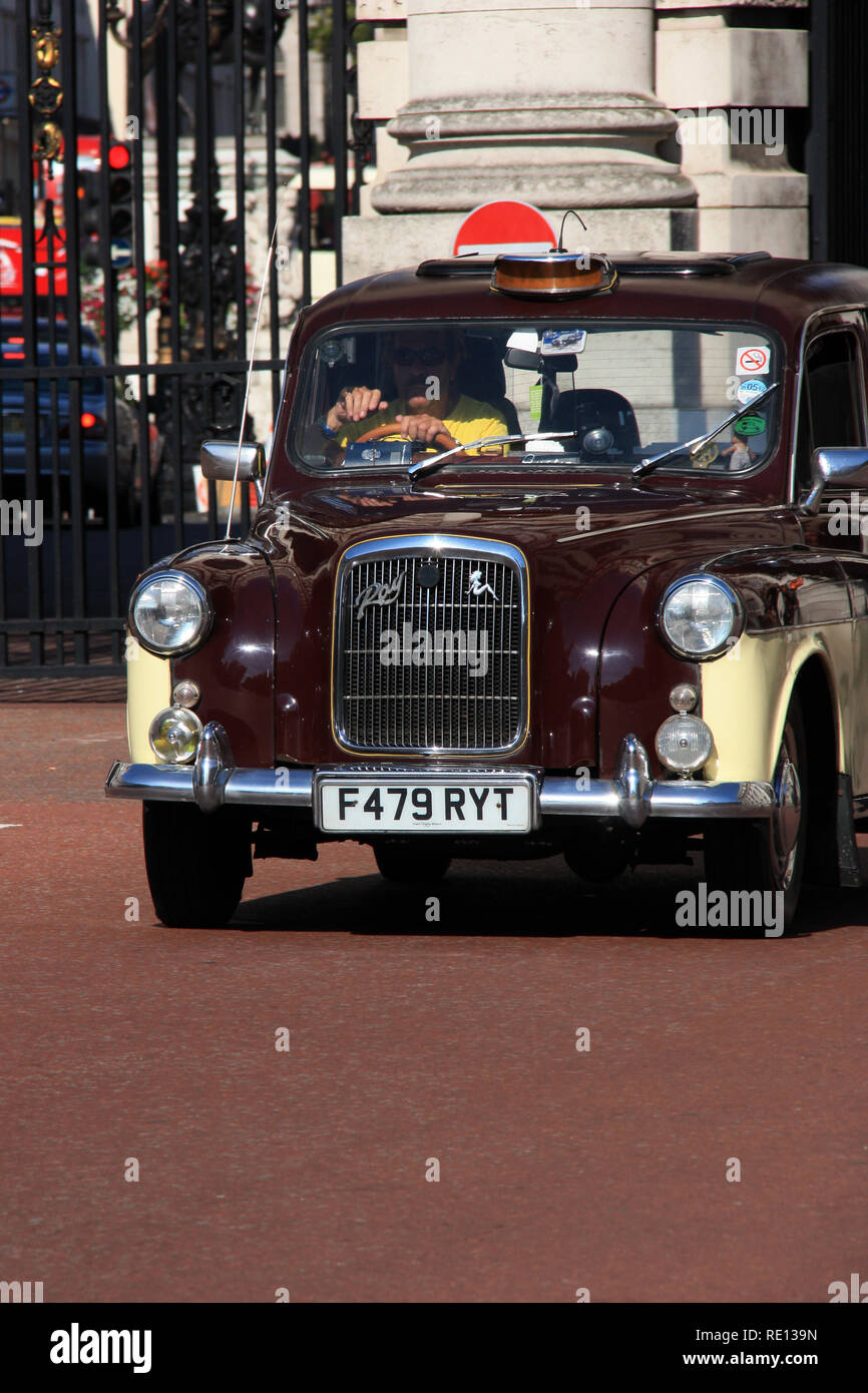 Typical British hackney carriage driving through Admiralty Arch in London, United Kingdom - Stock Image