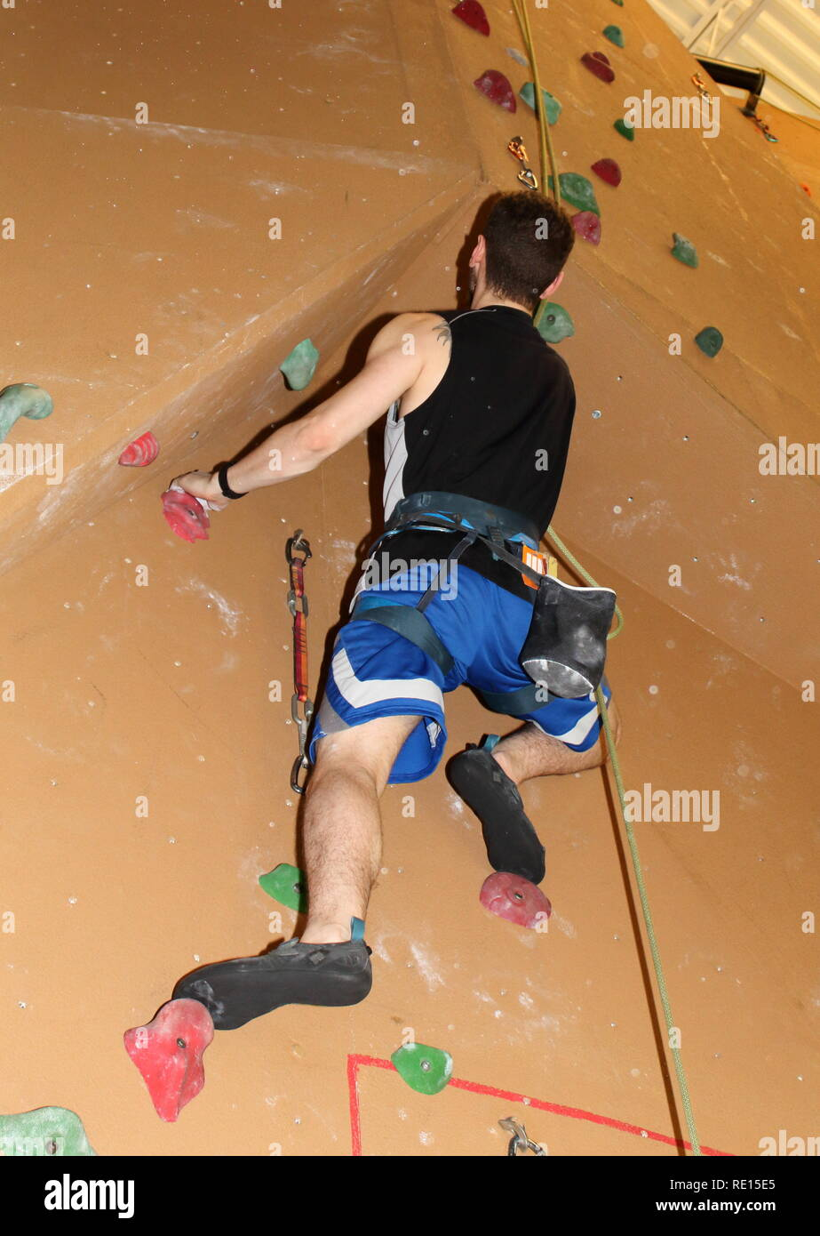Climber ascending brown wall on self belay - Stock Image