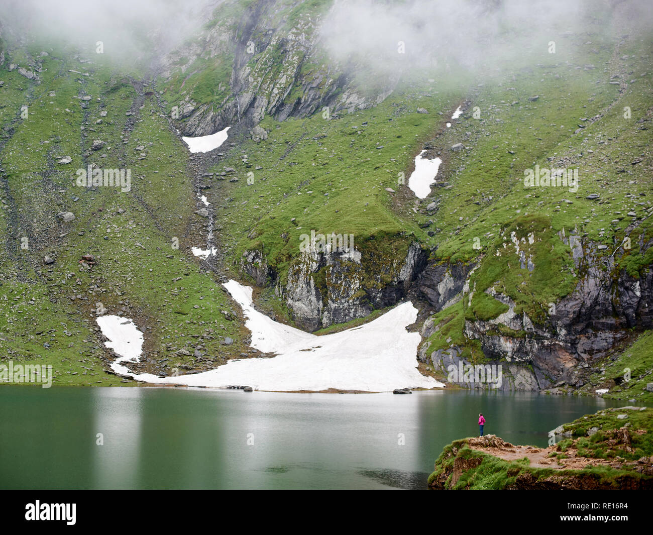 Mighty mountains are covered with fog and the lake at the foot, Transylvania, Romania. In the distance you can see a tourist girl who enjoys the majestic scenery Stock Photo