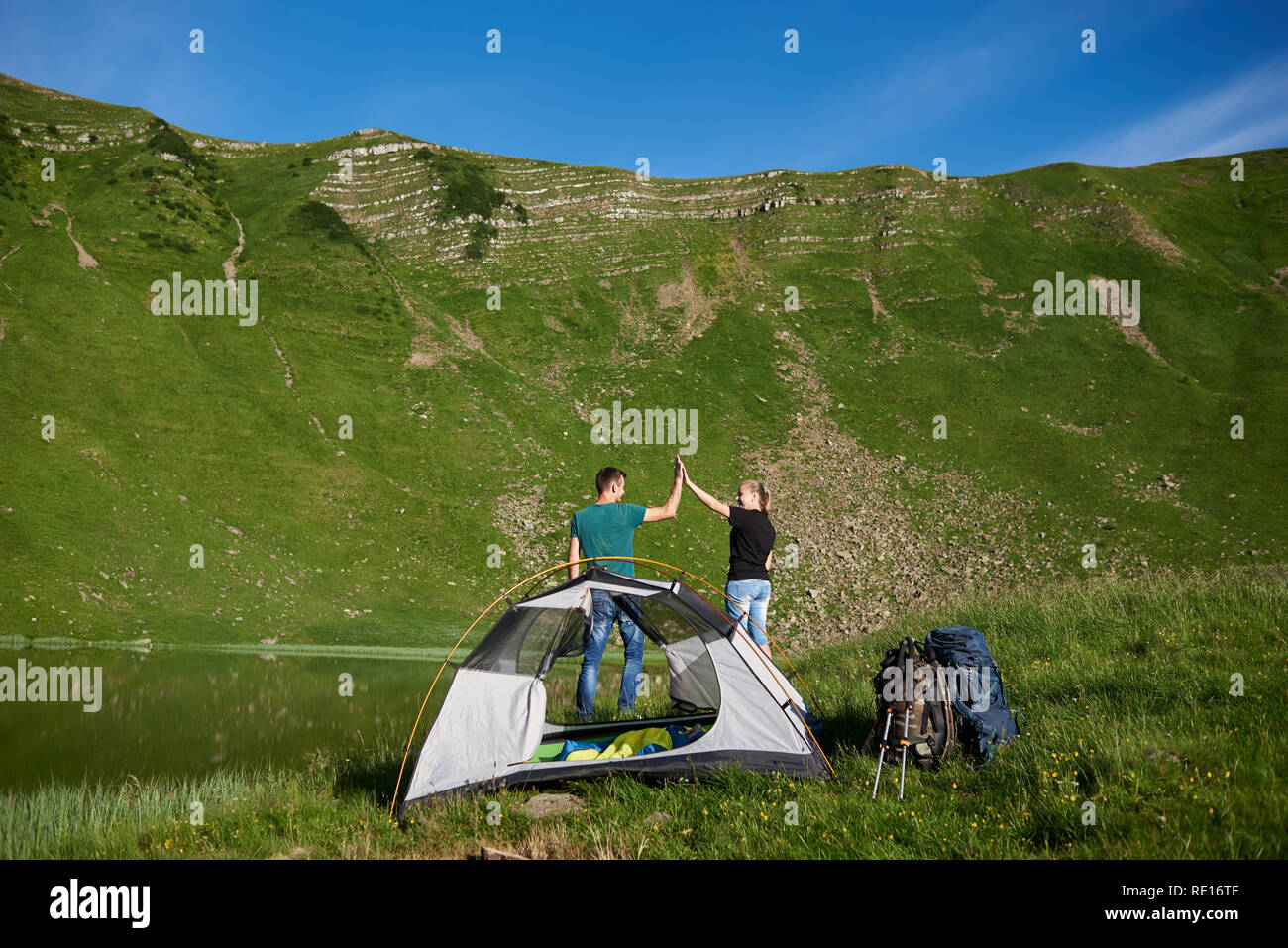 Happy couple giving high five near camping with a tent, backpacks and trekking sticks, against at mighty green mountain at the foot of which is a lake under a blue sky - Stock Image