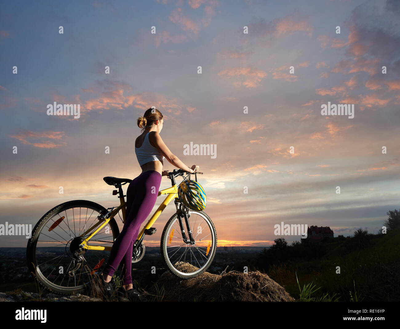 Slender woman with a mountain bike is standing on a hill under a beautiful sky at sunset against the background of the town in the distance. Helmet hangs on the handle of a bicycle - Stock Image