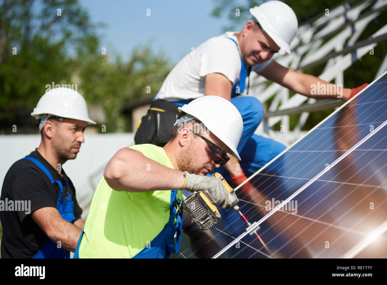 Three professional technicians installing solar photo voltaic panel to metal platform on blue sky background. Stand-alone solar system installation, efficiency and professionalism concept. - Stock Image