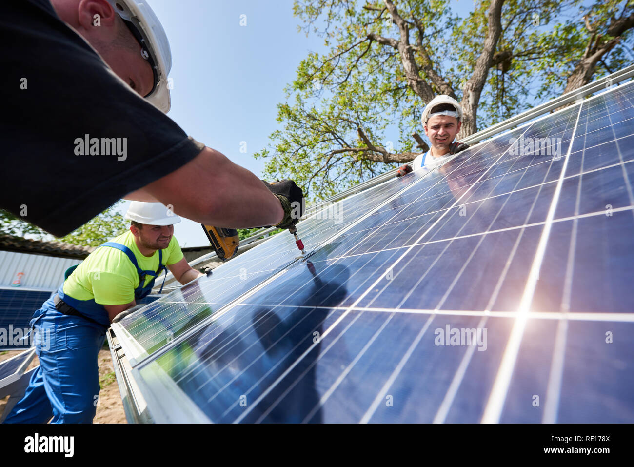 Team of three technicians working on exterior voltaic solar panel system installation in rural countryside on bright sunny summer day. Renewable ecological cheap green energy production concept. Stock Photo