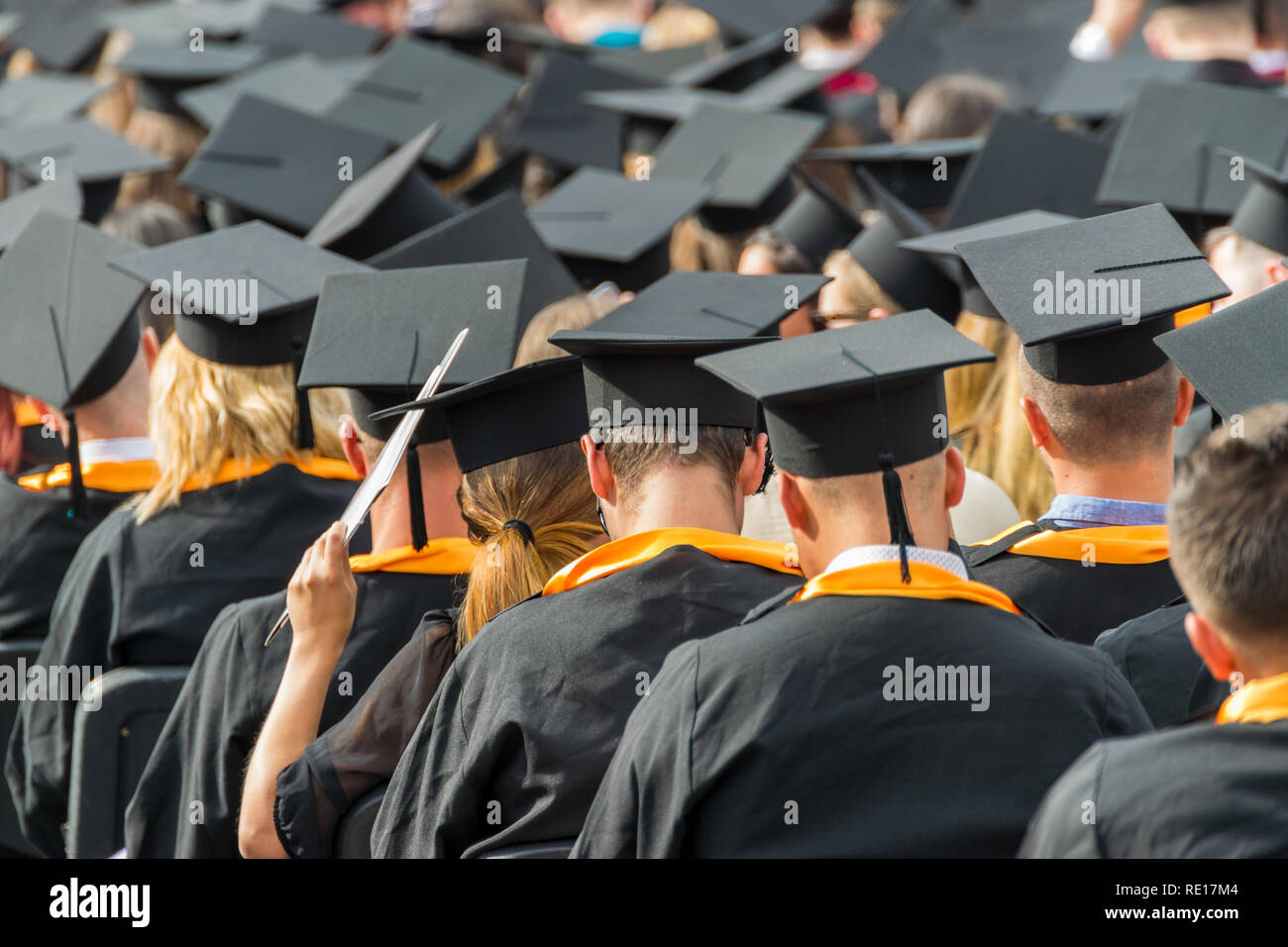 Yong student wearing graduation caps at a graduation ceremony. - Stock Image