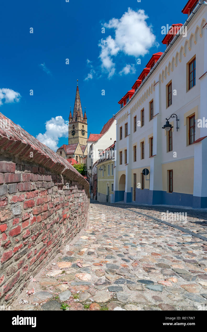 Sibiu, Romania - Beautiful street with Lutheran Cathedral of Saint Mary on a sunny summer day with blue sky in Sibiu, Romania. Stock Photo