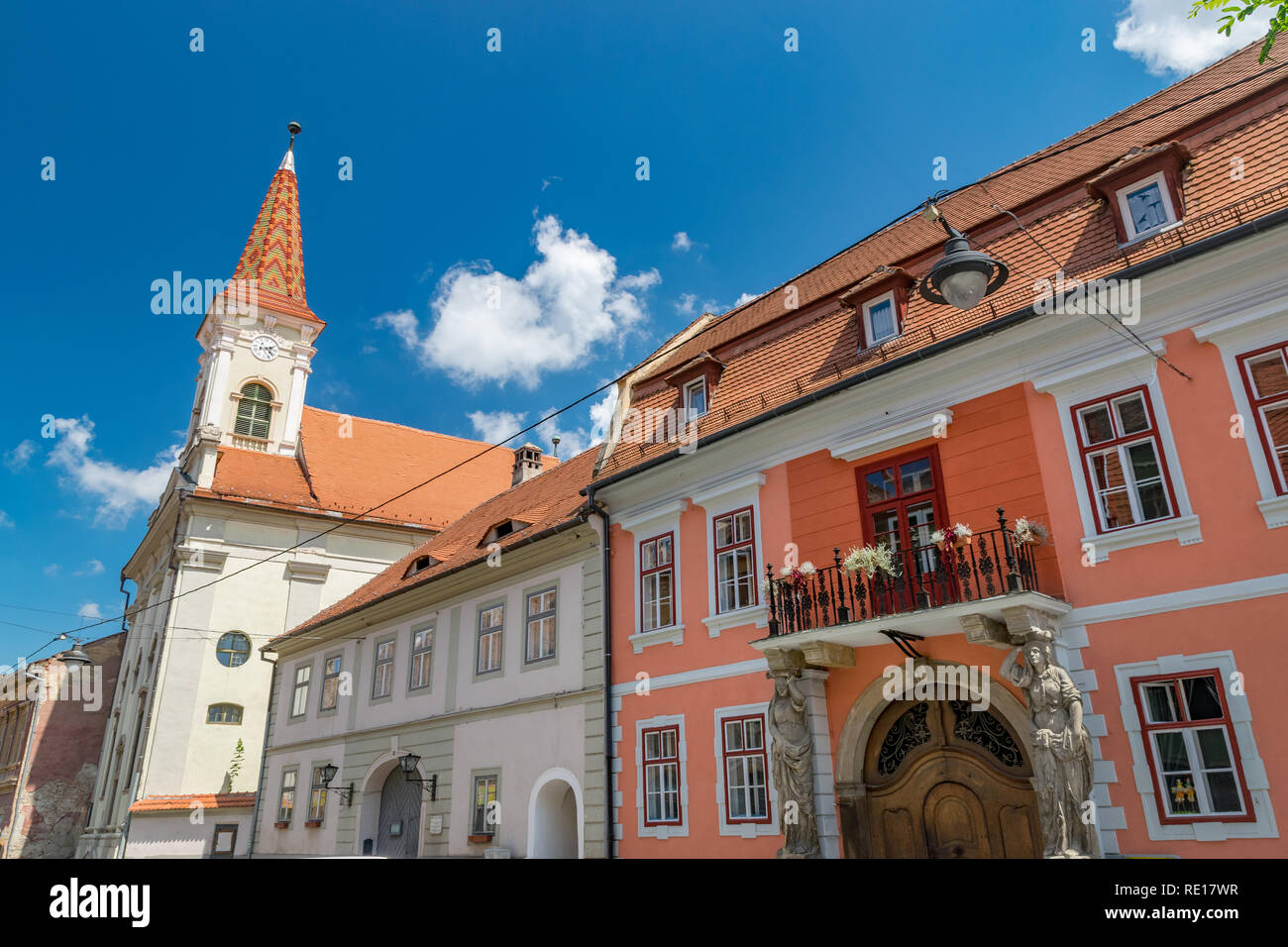 Sibiu, Romania - Beautiful street with Reformed Church and House with Caryatides on a sunny summer day in Sibiu, Romania. - Stock Image
