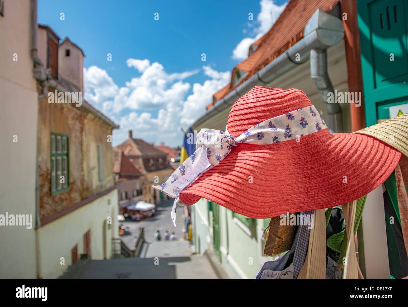 Pink women hat close-up on The Stairs Tower in a beautiful medieval town of Sibiu on a sunny summer day with blue sky, Sibiu, Romania. - Stock Image