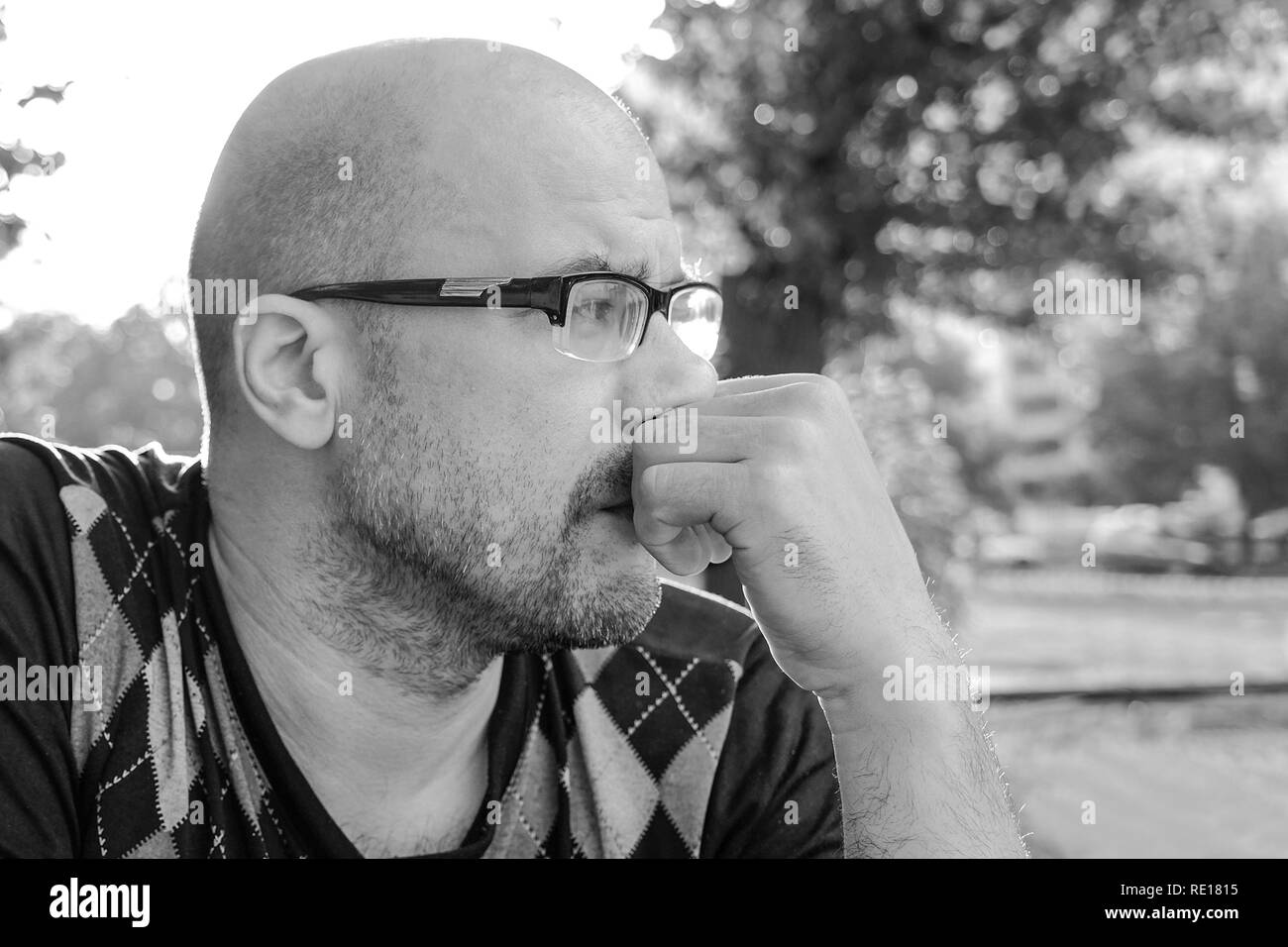 Black and white photo .The man with glasses is depressed . Problems in personal life and at work. Stress and depression. Migraine is a consequence of  - Stock Image