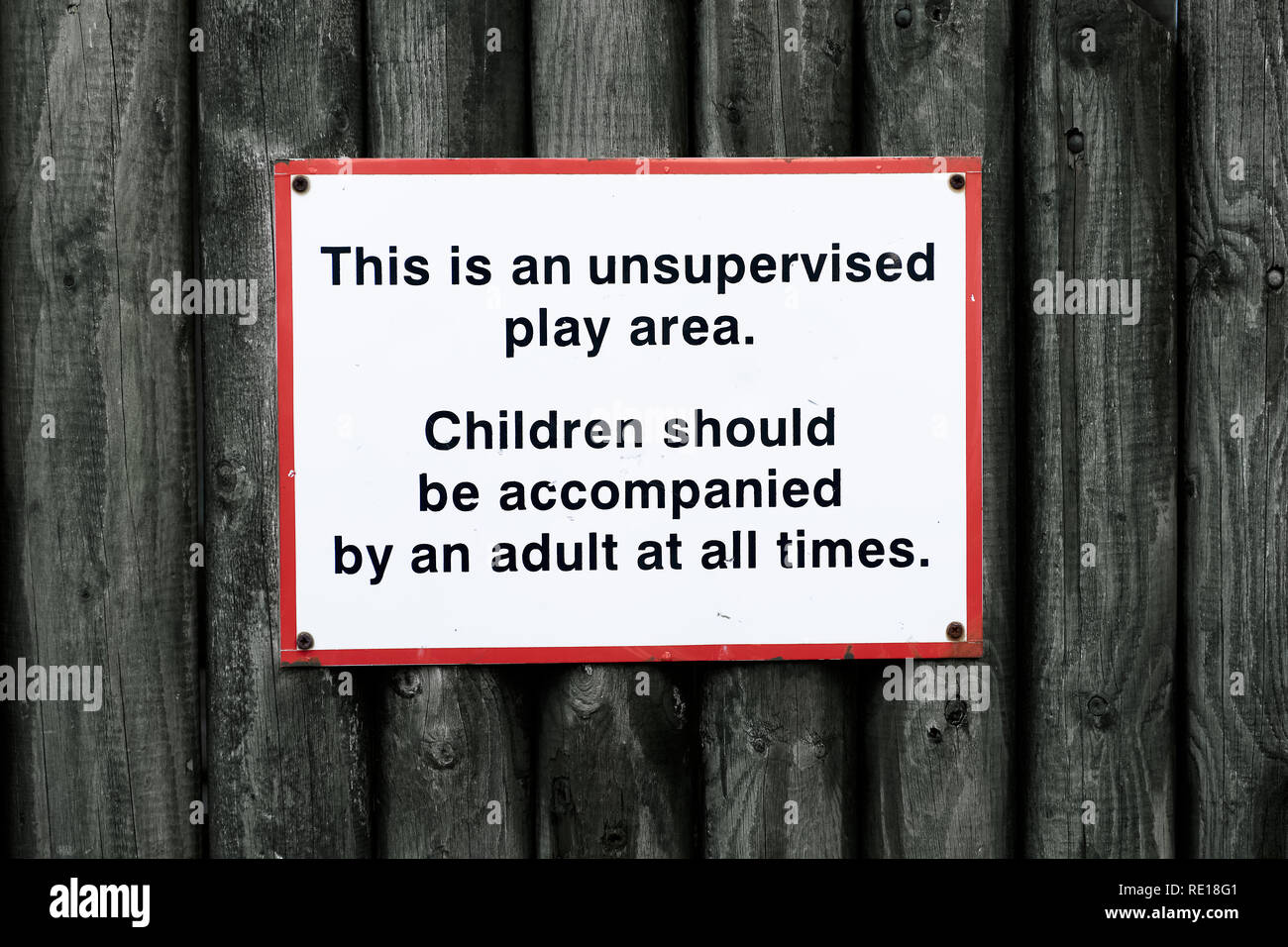 Children play area unsupervised accompanied by adult all times - Stock Image