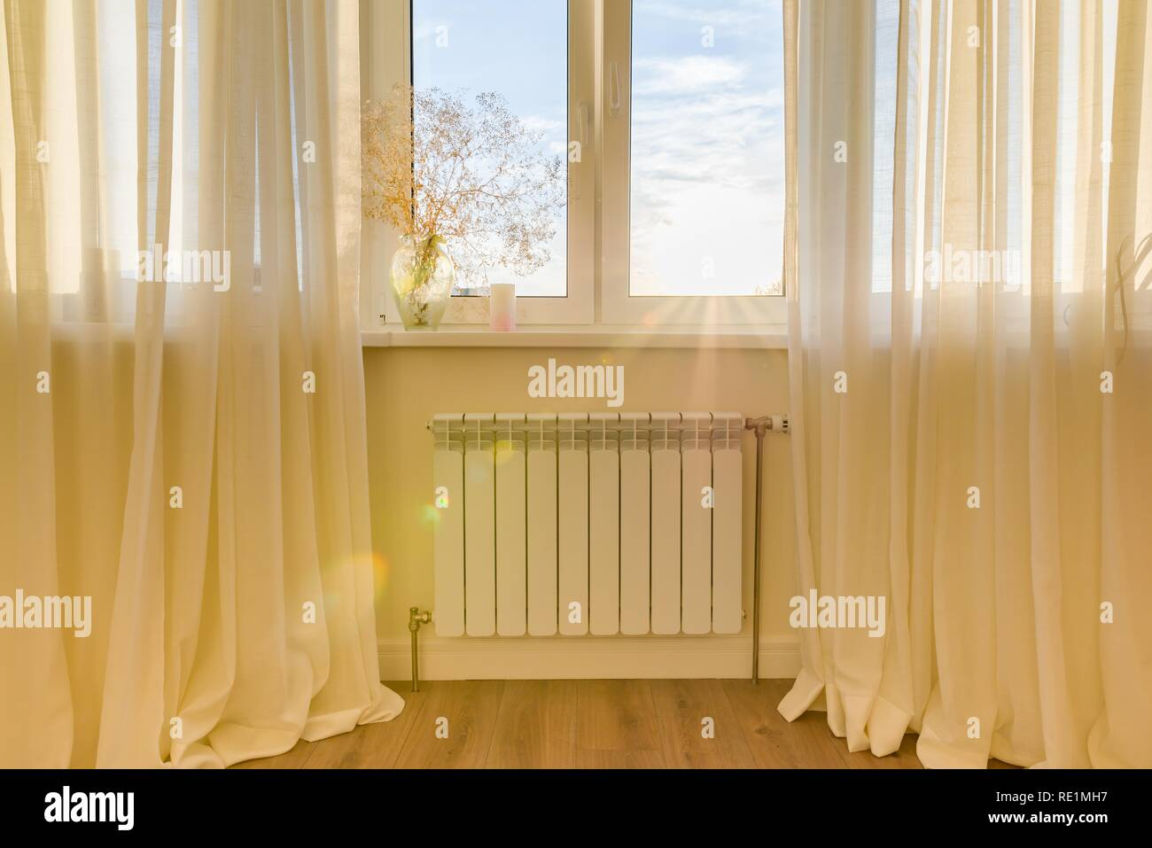 White radiator with thermostat in the apartment. Heater under the window - Stock Image