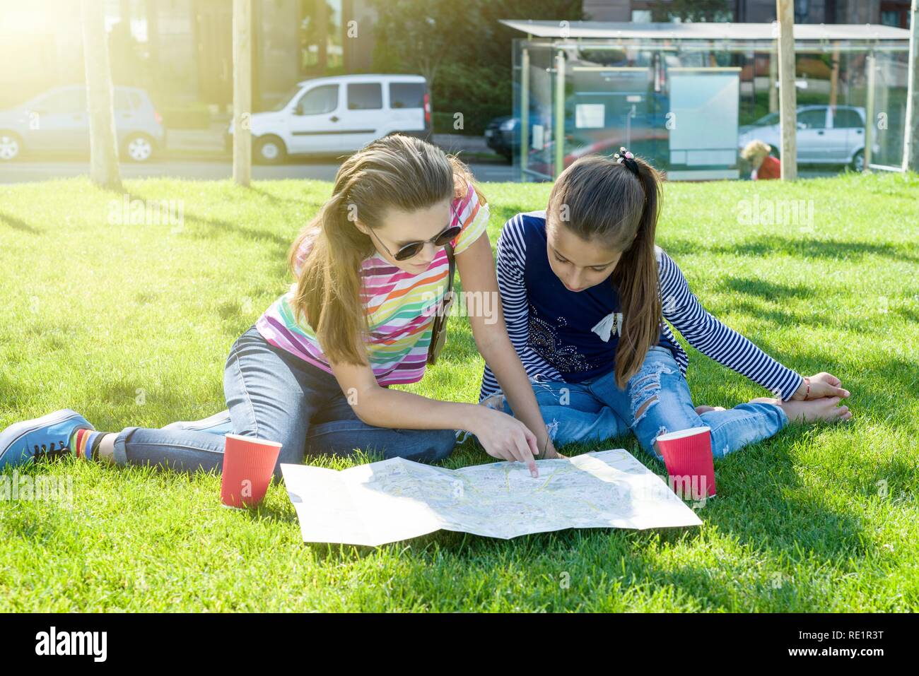 Young cute girls teens with map of european city outdoors - Stock Image