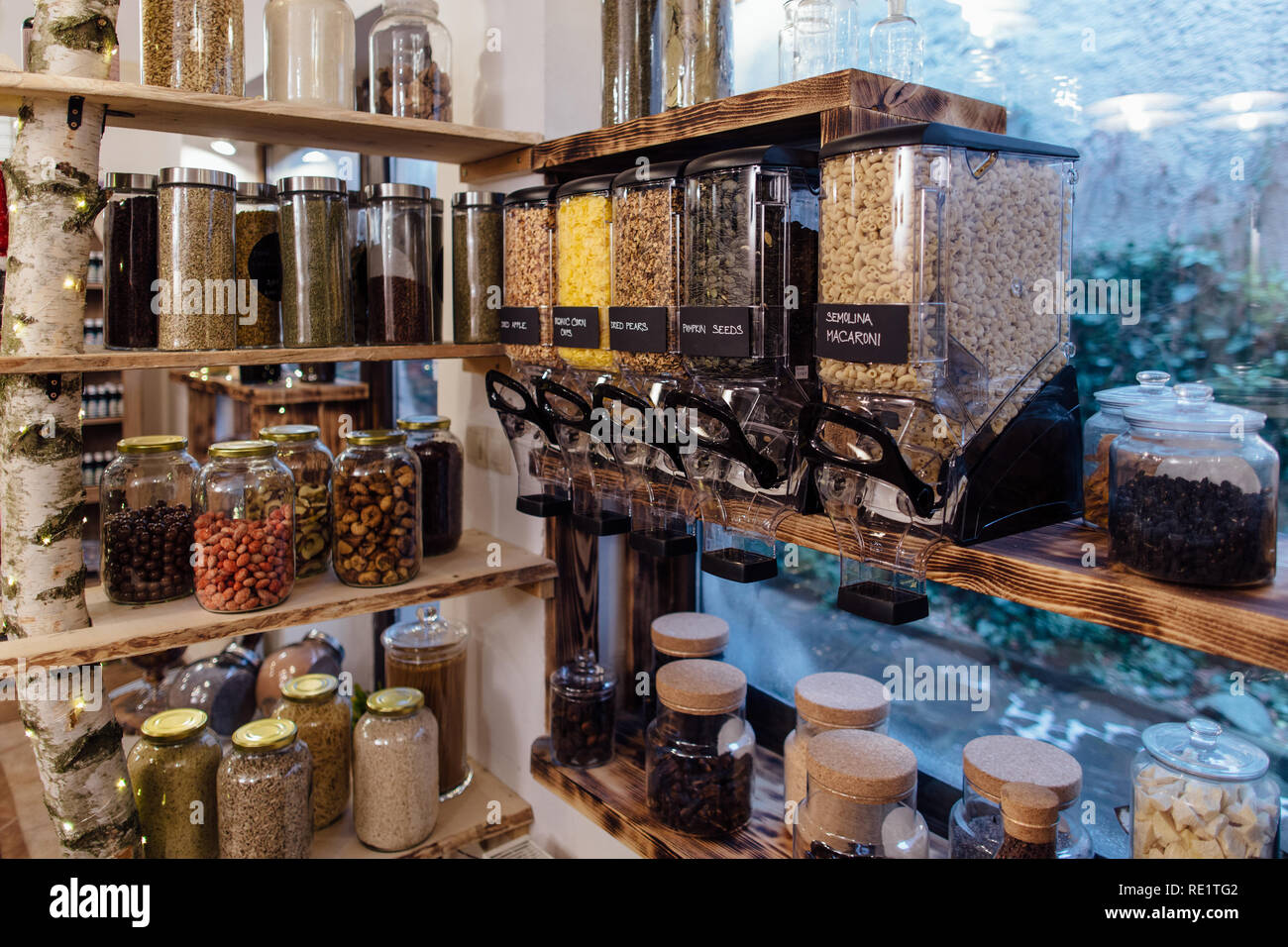 Organic shop interior. Display of glass jars on shelves filled with fresh and dry produce in grocery store. - Stock Image