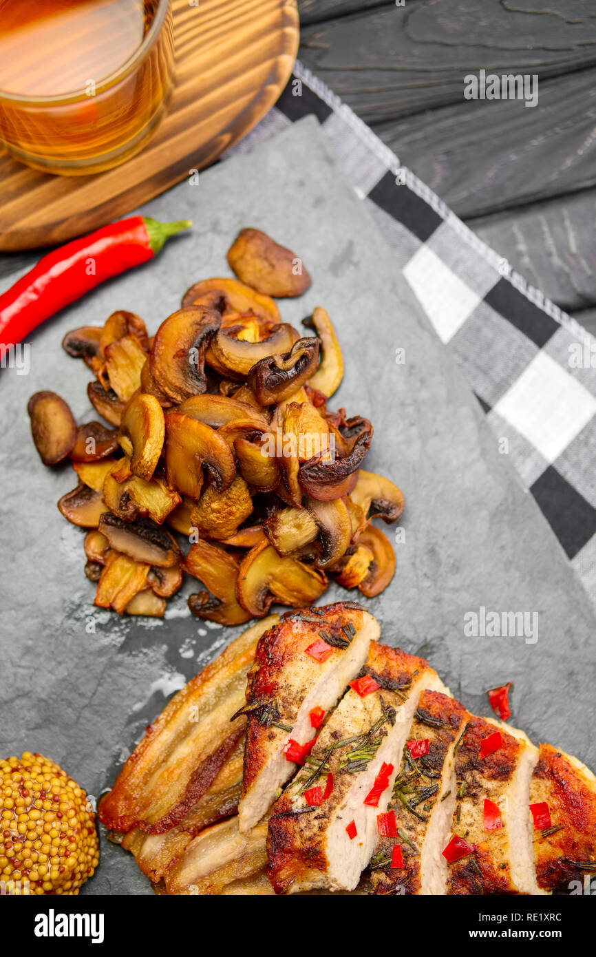 Top view of fried fillet with mushrooms and slices of bacon served with pepper moonshine. Unhealthy but so tasty country food. - Stock Image
