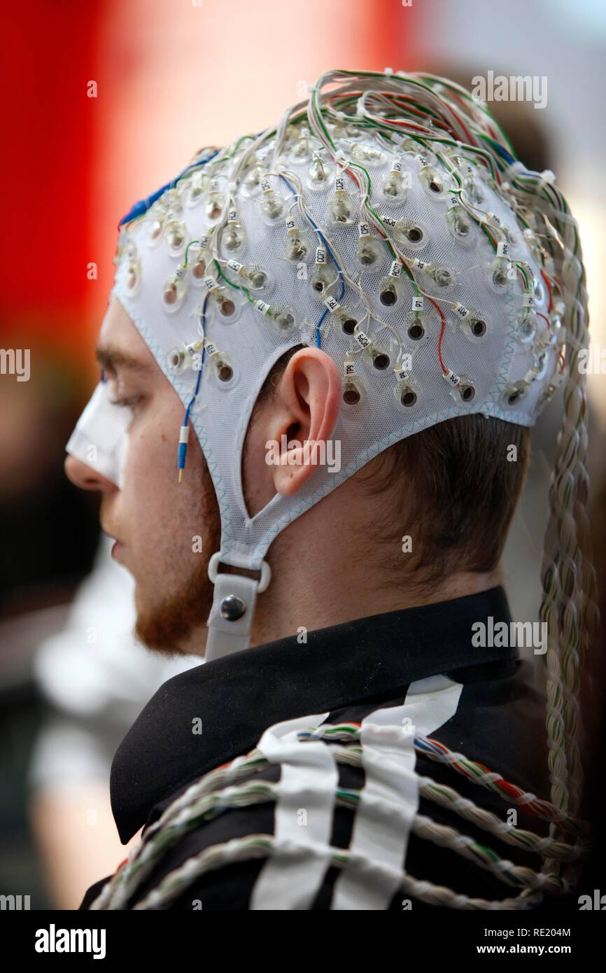 Control of machines and computers through brain activity, electrodes on the scalp detect brain activity and give signals to a - Stock Image