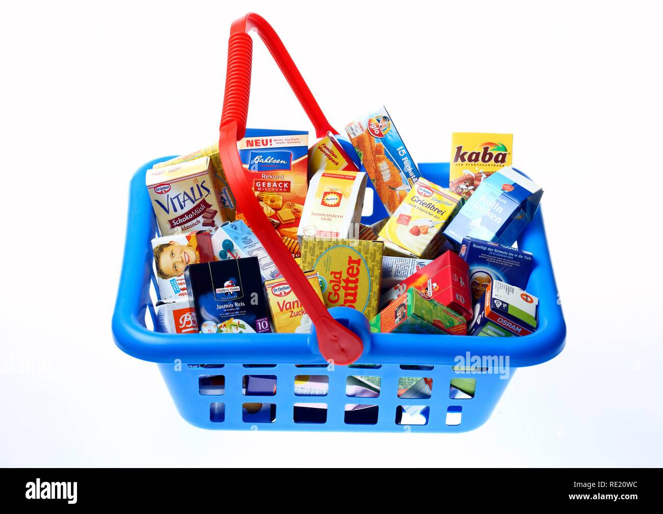 Toy shopping basket filled with mini packaging from a children's shop - Stock Image