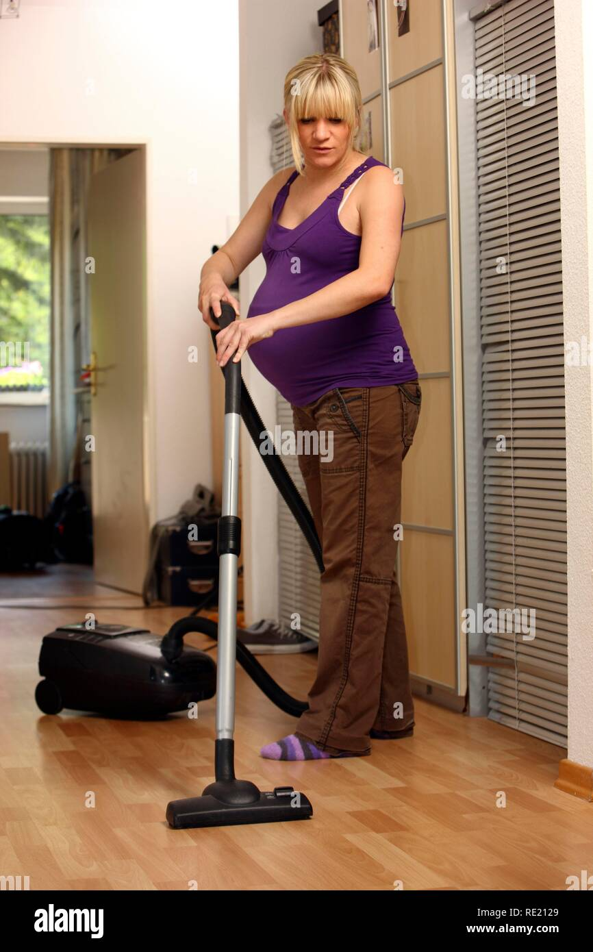 Pregnant woman, 9th month, at home, doing light housework, vacuuming - Stock Image