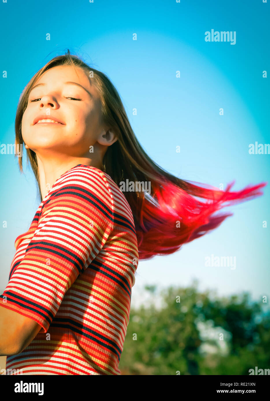 Tween girl swinging and twirling her trendy pink tipped blond hair outside - Stock Image