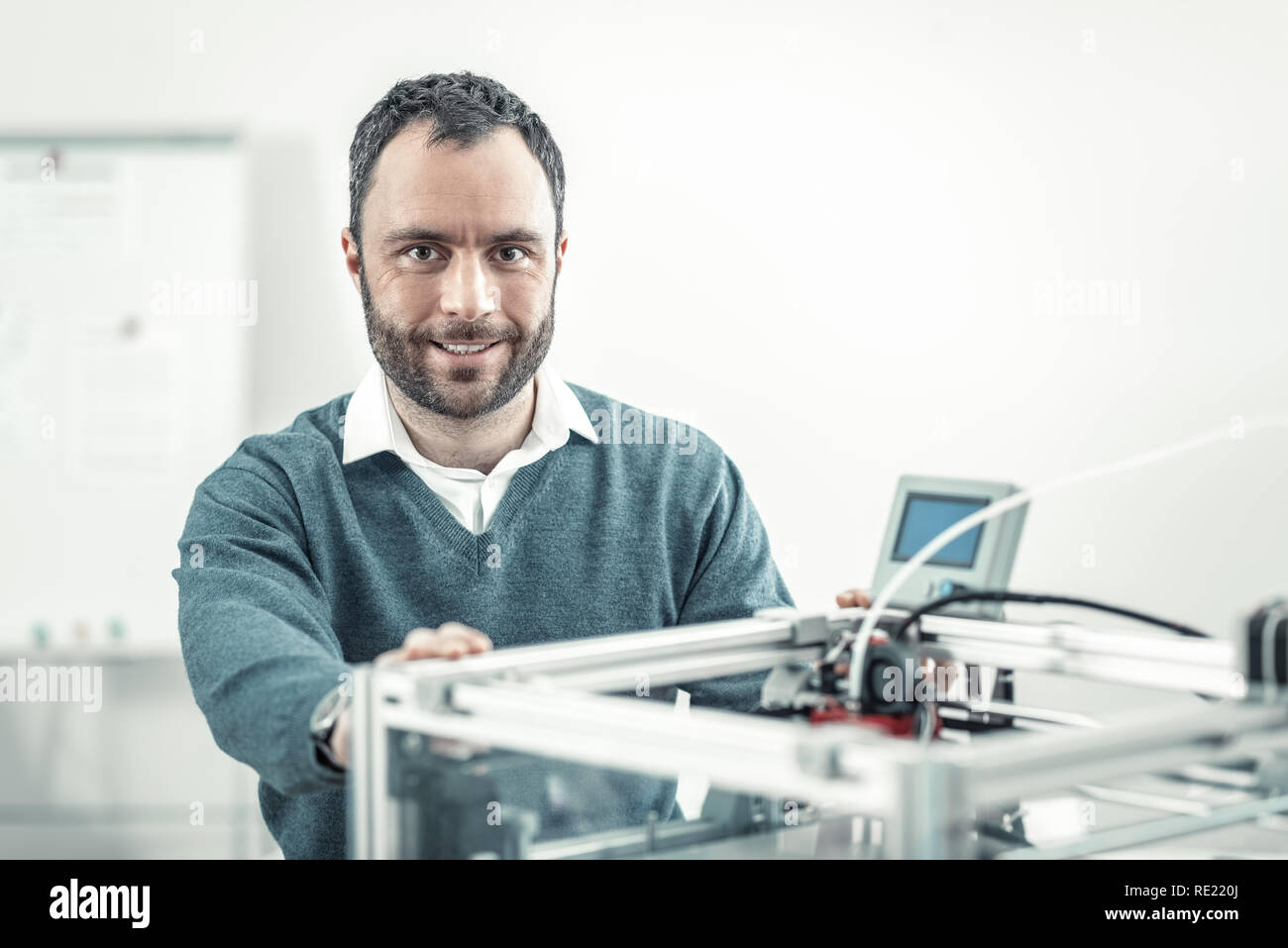 Delighted adult nice man smiling near 3d printer Stock Photo