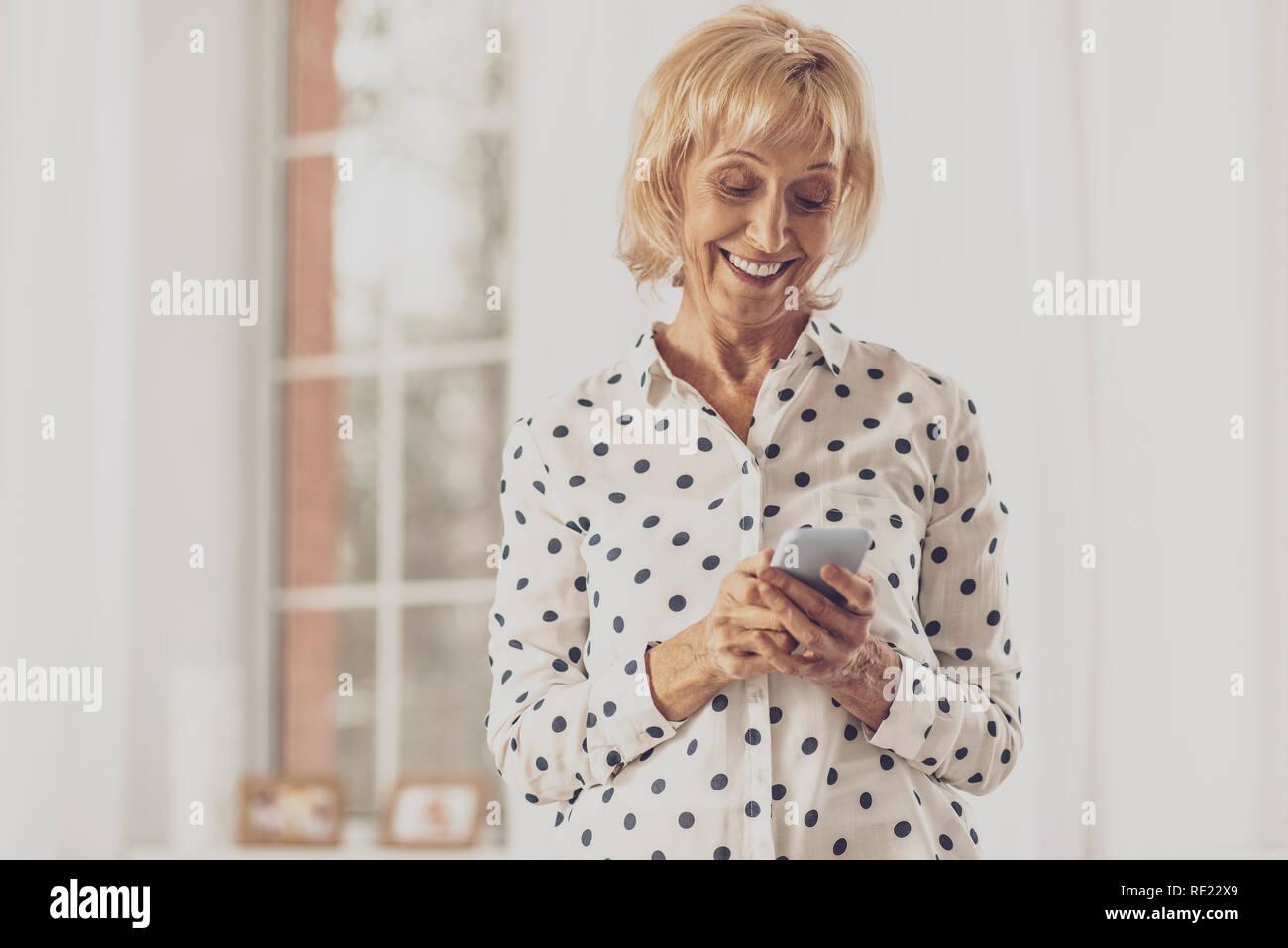 Joyful housewife typing friendly message - Stock Image