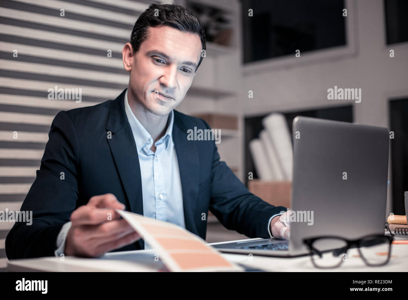 Smart handsome businessman sitting at the laptop - Stock Image