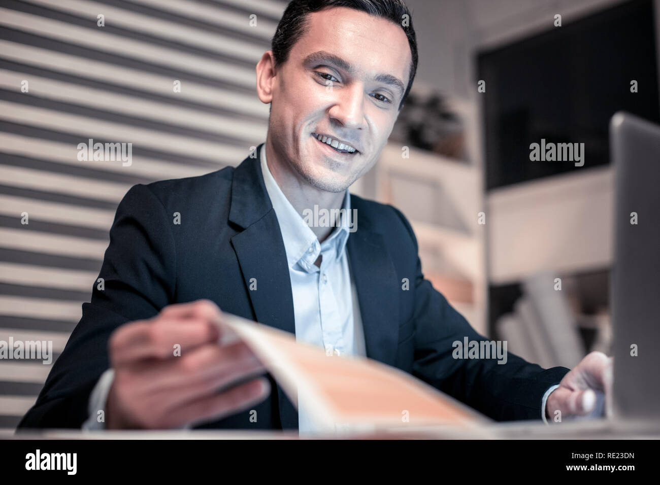 Cheerful positive smart man being at work - Stock Image
