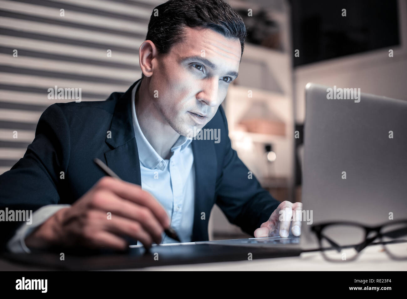 Professional smart man taking notes while working - Stock Image