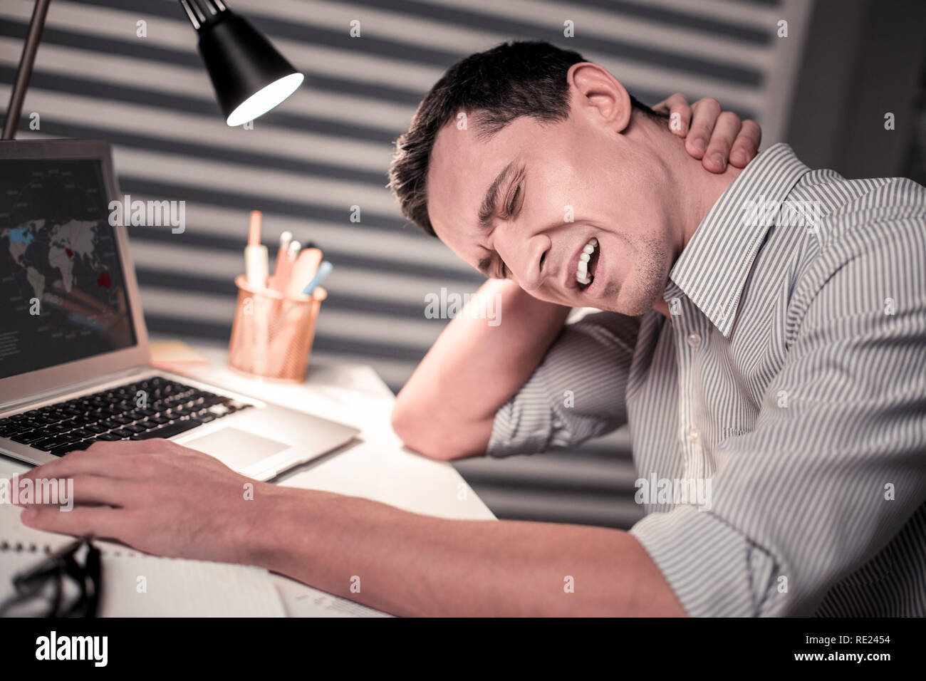 Cheerless unhappy handsome man touching his neck - Stock Image